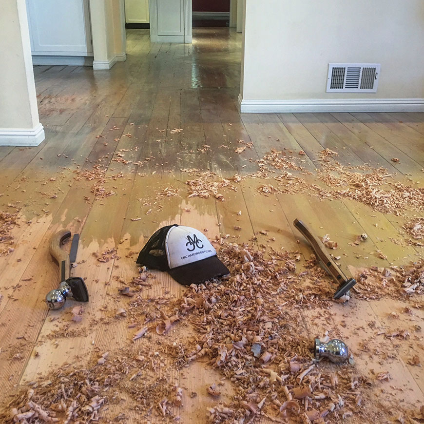 Hand scraping hardwood floor in West Hollywood